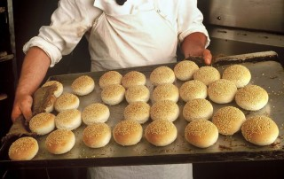 baker holding a tray of buns