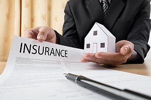 homeowners insurance expert holding an insurance document and home in his hands