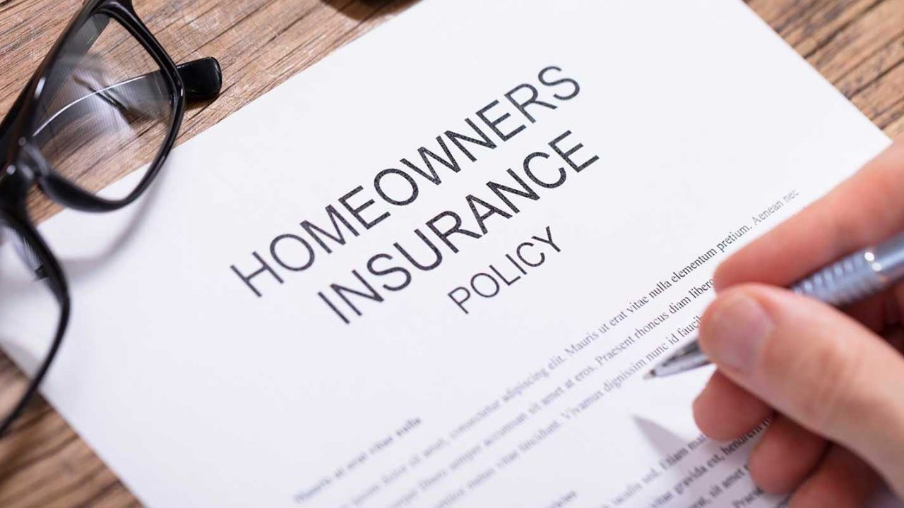 Man signing a homeowners insurance policy