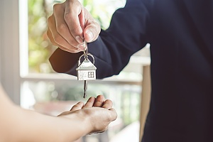 landlord who is covered by umbrella insurance handing over the keys to a home