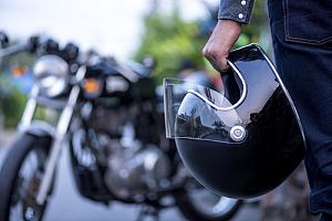 Rider with motorcycle insurance holding helmet