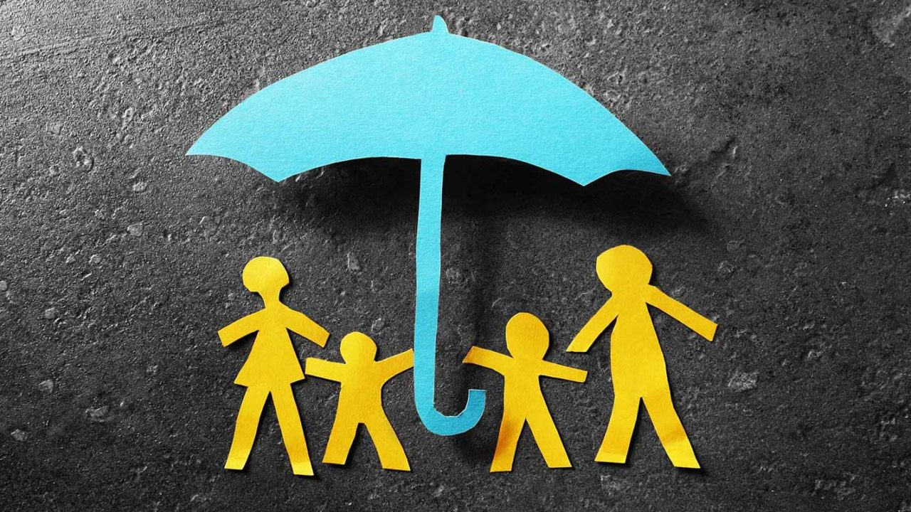 Paper family underneath a paper umbrella
