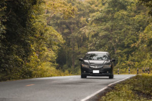 Car driving on country road with personal insurance