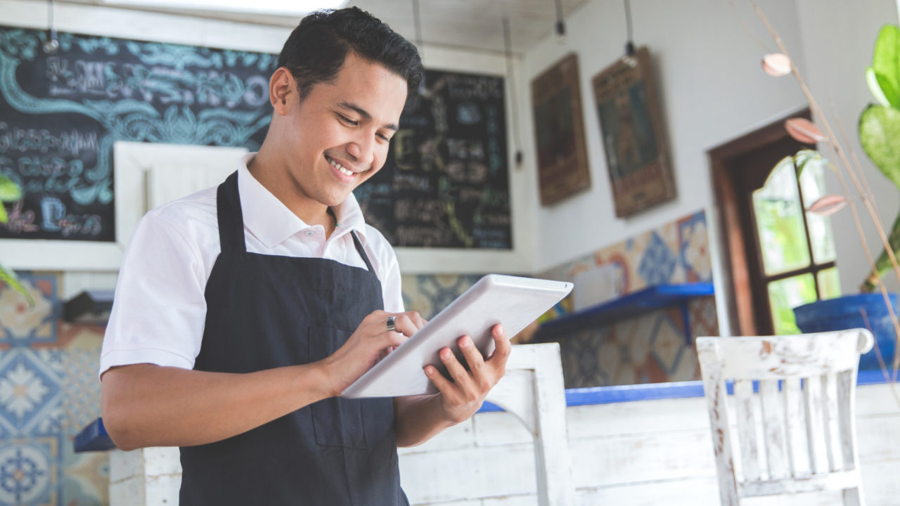 the baker in his property uses tablet to sign up for bakery insurance