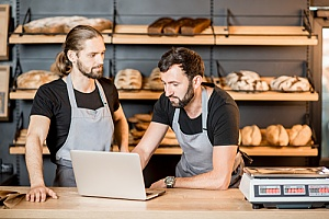 two bakers taking inventory on a work laptop