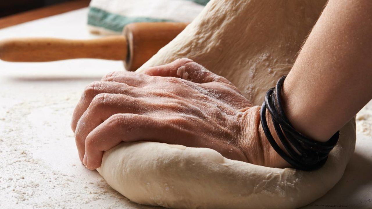 after attaining homeowners insurance the baker stretch the dough in the makeshift home bakery