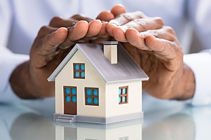 an insurance broker holding his hands over a model home representing home insurance