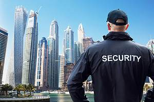 A male security guard stood with arms akimbo. Security guard insurance coverage is required in most states