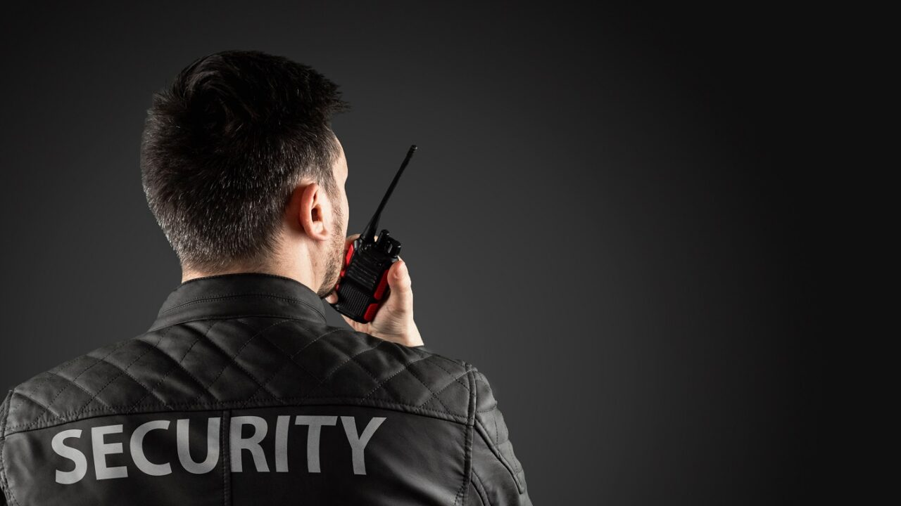 Security Guard in Black Jacket and Wireless in Hand