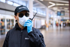 a security guard wearing a face mask and gloves to protect against liability