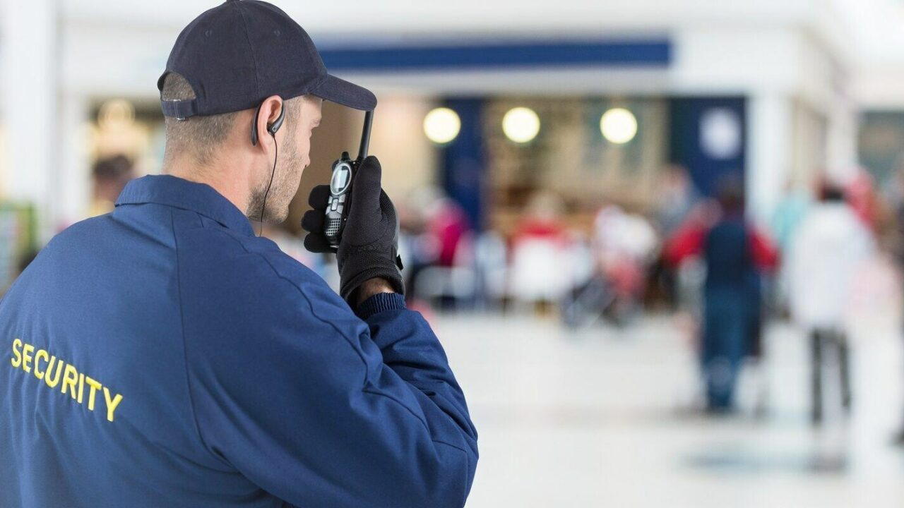 digital composite of Back of security guard with walkie talkie against blurry shopping center security guard insurance