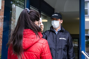 security guard checking temperature at building entrance