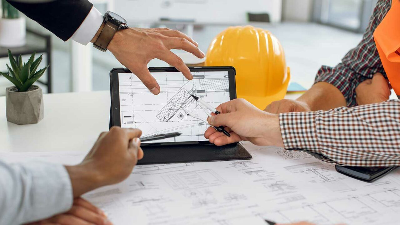 Contractors with general contractor insurance looking at blueprint